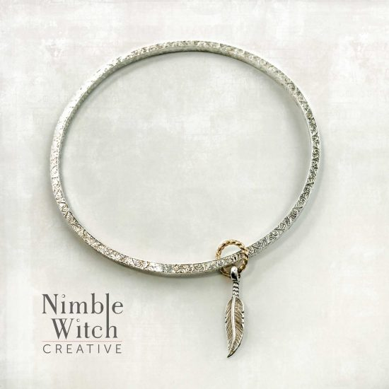 Silver bangle bracelet with feather charm